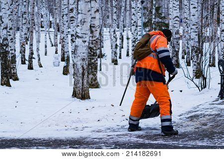A man in working clothes with a shovel removes snow on the track in the park in winter landscape