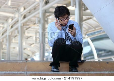 Unemployed young Asian man looking for job in mobile smart phone. Unemployment concept.