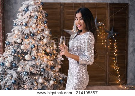 Beautiful asian woman in beautiful glitter dress with a glass of champagne. Christmas party. Christmas Eve. X-mas, winter holidays and people concept