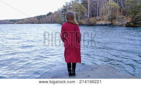 Young Woman Relaxing near Lake. Romantic beautiful woman enjoying her time and peaceful nature. Calm and cozy evening.