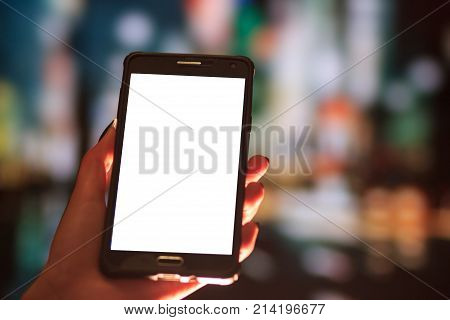 Woman using her Mobile Phone in the street, night light Background , soft focus picture.