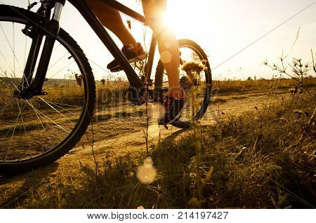 man cyclist driving dirt road by mountain bike sunset time