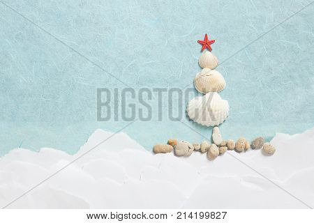 Starfish and seashells in the shape of Christmas tree on paper background. Christmas tree from seashells with rocks shooted from above
