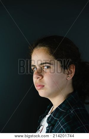 Headshot portrait of defiant teenager looking at camera side view