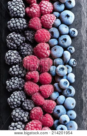 Frozen berries on black slate. Blueberry raspberry black berry. Top view. High resolution product.