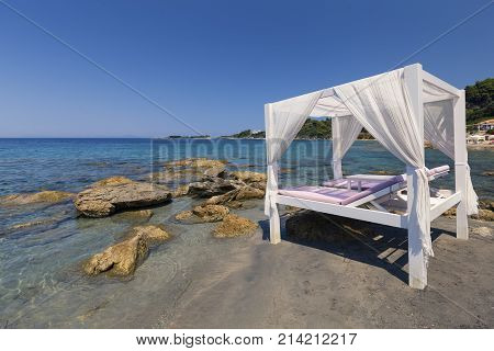 Luxury white bed on a beach in the Mediterranean