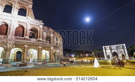 Roman Colosseum and Constantine Arch by night with tourists and photographers with a bride for marriage night photo shooting in Rome, Italy.