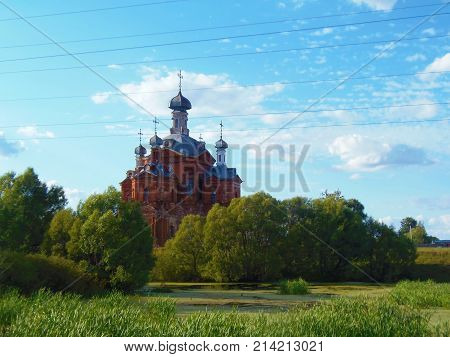 Russia, the Ryazan region, the village of Pokrovo-Gagarino, pond overgrown with duckweed, a temple of stone with five domes