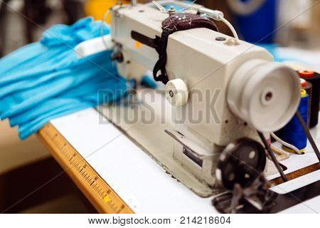 Industrial sewing machine with textile on desk