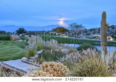 Moonrise over Four Peaks Mountain Arizona with Sonoran Desert contrasted by green grass and lake in foreground.