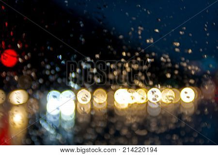 water drop on the obscured glass raining drop and red blue color road light bokeh Abstract urban defocused background rain drops on car window