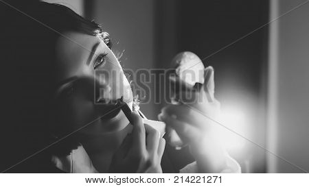 Black and white portrait of beautiful young woman applying lipstick while looking in small mirror. Retro or vintage style. Attractive brunette girl.