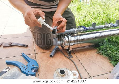 Series Of Plumber Fixing Up Ourdoor Water Filter With Pvc Piping