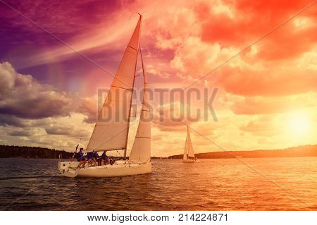 Sailing yacht race, regatta. Sailboat on the background of a beautiful sunset. Team athletes participating in the sailing competition.