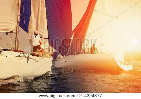 Sailing yacht race, regatta. Sailboat at sunset. Team athletes participating in the sailing competition. Recreational Water Sports.