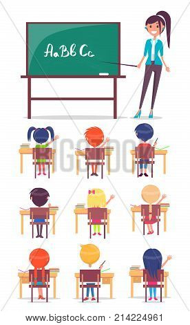 ABC lesson in primary school. Children sit at desk and study alphabet at the lesson, teacher stands near blackboard with pointer
