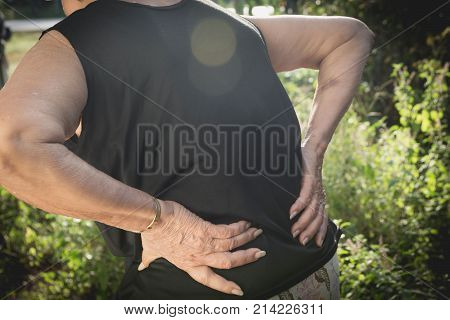Old woman suffering from backache spinal injury and muscle issue problem at outdoor.