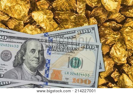 One hundred dollar banknotes on gold mine close up. Mining industry concept with dollars and gold