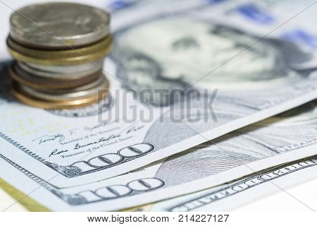 One hundred dollars and coin stack close up with selective focus