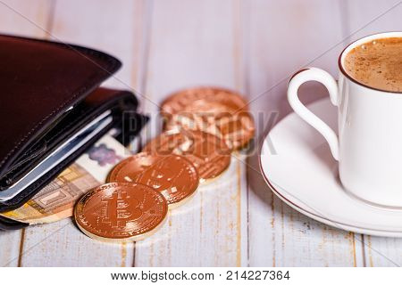 The picture of bitcoin wallet on a light background symbolizes elements of virtual economy. A concept of storage of electronic currency into digital wallets. A cup of coffee is coffee mood