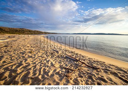 Summer Day At The Beach Background. Warm sunny summer day on the shore of Lake Superior with a wide sandy beach and blue water horizon. Horizontal orientation wide angle with copy space.