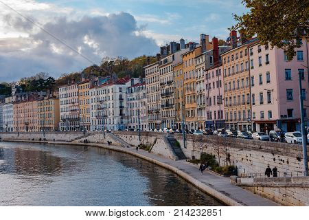 Lyon France -- November 5 2017 -- People cars and colorful buildings on the bank of the Saone River in Lyon France. Editorial Use Only.