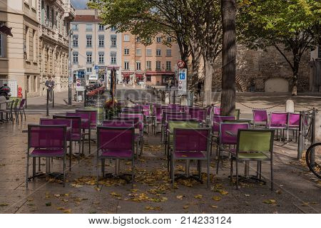Lyon France -- November 6 2017 -- Purple and green chairs and tables are set up for outside dining in the old city section of Lyon. Editorial Use Only.