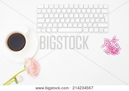 A white keyboard and a cup of black coffee on a white background. Styled mockup