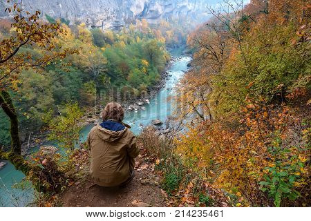 Male traveler is sitting on the edge of abyss above vast forest territory in autumn