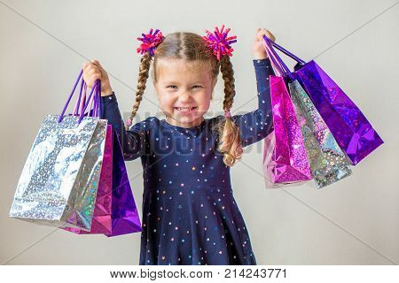 Smiling little girl with shopping bags with gifts. Happy child holds a lot of shopping bags with gifts. Black Friday sale holidays concept. Kids shopping