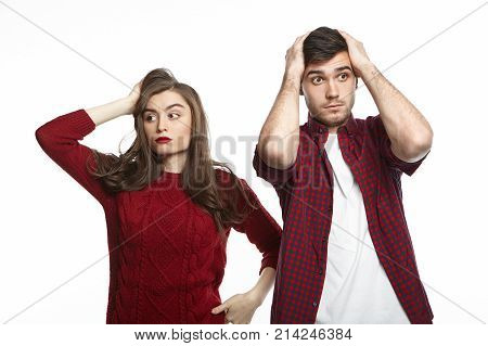 Portrait of fearful shocked young married man and woman feeling frustrated while facing financial stress holding hands on heads and trying to come up with solution to pay off all their debts
