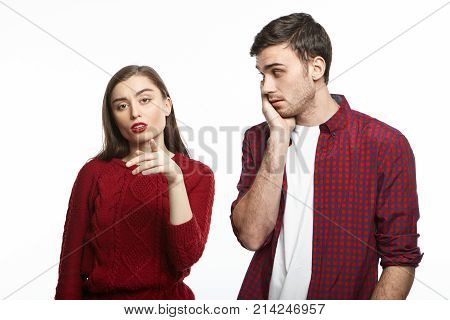 Human facial expressions emotions love and relationships. Elegant young lady pointing finger at camera having suspicious look her man standing next to her holding hand on cheeks feeling worried