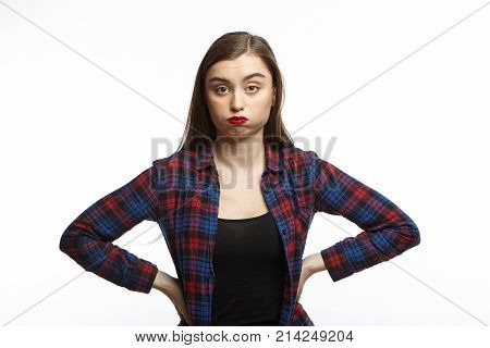 Picture of annoyed young woman wearing plaid shirt over black t-shirt holding hands on her waist and puffing her cheeks feeling fed up and puzzled with something irritatting. Mimic and grimace