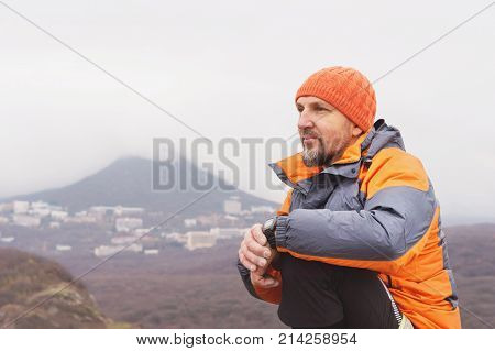 Hipster - a climber in a down jacket and a knitted hat sits and rests on top of a rock with a view of the autumnal ponamram of neighboring mountains and cities in cloudy weather.