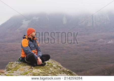 Hipster - a climber in a down jacket and a knitted cap sits and meditating meditates looking at the autumnal ponamram of neighboring mountains and cities in cloudy weather.