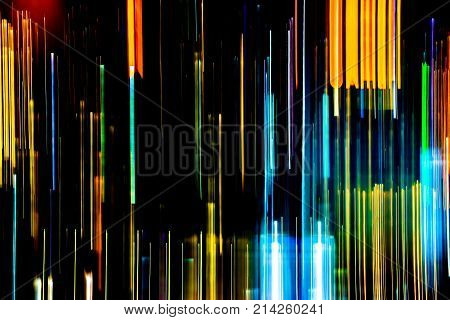 Abstract of multicolored city lights beams in motion Moving colorful lines or light painting LED building abstraction on busy city Light trails Rainbow and chaos black background. Vertical desigh