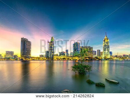 Ho Chi Minh City, Vietnam - November 16th, 2017: Riverside City sunrays clouds in the sky at end of day brighter coal sparkling skyscrapers along beautiful river in Ho Chi Minh City, Vietnam