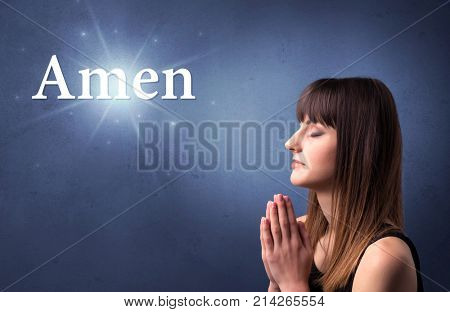 Young woman praying on a blue background with the word Amen written above her