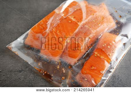 Marinated slices of salmon fillet in plastic bag on grey background