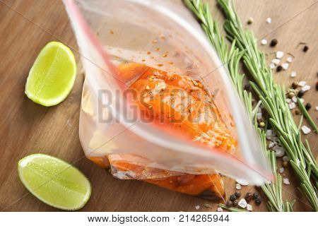 Marinated slices of salmon fillet in plastic bag on table