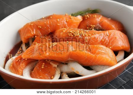 Casserole dish with marinated slices of salmon fillet on table, closeup