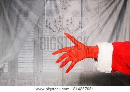 Santa Claus or Grinch hand in a red glove and Santa Arm.