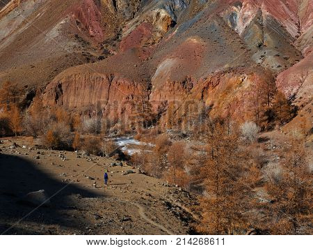 Fantastic Martian landscape. A small silhouette of a girl against a background of huge mountains. Reverence of the power of the earth. Mars. Red mountains. Mountain Altai.