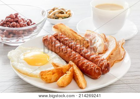 English breakfast with smoked sausages, scrambled eggs, bacon, mushrooms, toast and beans. Tea with milk. Breakfast on a white plate on a light background. Backlight