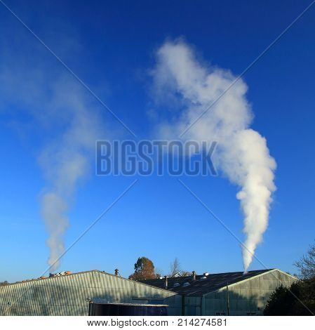 Smoke or steam from factory against blue sky