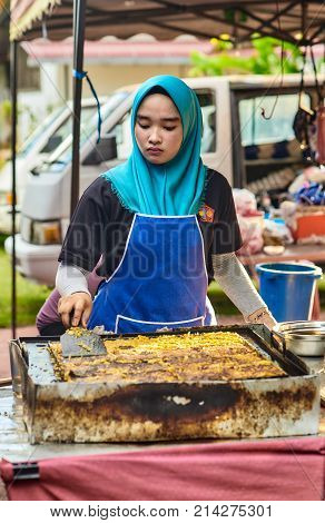 Langkawi Malaysia - November 2017. Young asian woman cooking of Murtabak - traditional asian cakes with filling inside. Classic asian street food from Langkawi island in Malaysia.