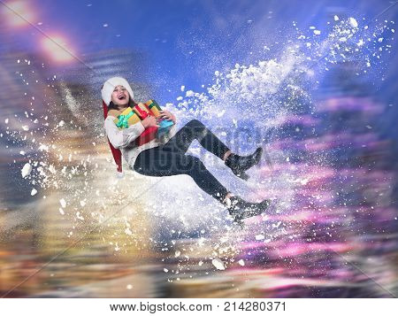 Amazing emotional portrait of a girl in a fantastic whirl of snow. Christmas hat gifts in hands. Happy girl laughing