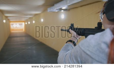 Woman shooting with a Machinegun at the shooting gallery, close up