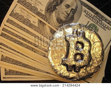Bitcoin real metal coin is on one hundred dollars bills or banknotes. It means hot price or value and high exchange rate of crypto currency on market. It also means investments with financial risk