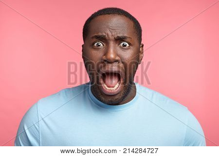 Excited African American Man Screams In Panic, Gaze With Bugged Eyes, Shocked To Hear Bad News. Surp